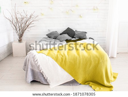 light, white, spacious bedroom with a large bed, in the Scandinavian style. Color of the year 2021