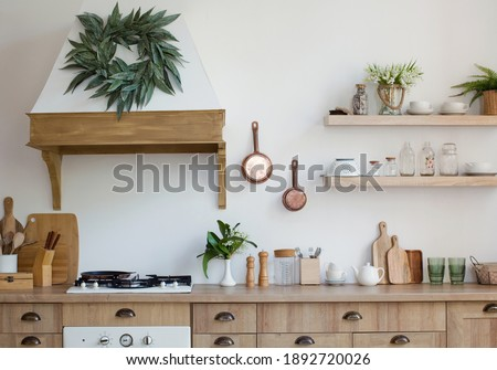 Light wooden kitchen interior with kitchen utensils on the shelves and on the wall. Beautiful kitchen interior design