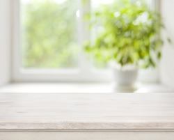 Light wooden table on defocuced spring window background.