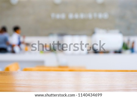 Light wooden top table in front of blurred background of cafe or coffee shop and bar.The table for display or lay down goods for online advertisement.