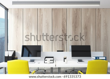 Light wooden wall open space office interior with a large window, a long table with two computer monitors on it, blue and red chairs. Close up. 3d rendering mock up
