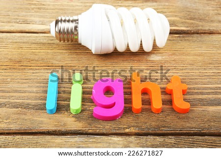Light word formed with colorful letters on wooden background