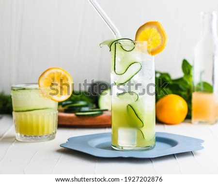 Light yellow green gin cocktails in a highball glass and rocks glass surrounded and garnished with cucumbers and lemon. Foto stock ©