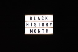 Lightbox with text BLACK HISTORY MONTH on dark black background. Message historical event. Light