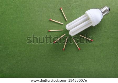 Lightbulb and matchsticks shaped as sun symbolizing renewable solar energy