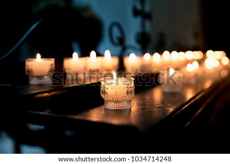 Lighted candles in the Church on the table on the background of cross reflection, religious tradition, prayer