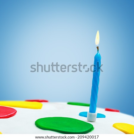 Lighted candles on a birthday cake on a blue background