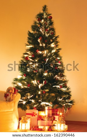 Lighted Christmas tree with presents underneath in living room #162390446