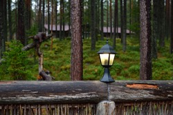 Lighted outdoor lamp on a wooden fence against the beautiful autumn pine forest. Russia, Karelia. Focus on foreground