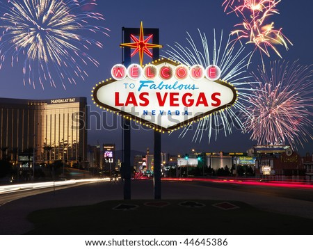 Lighted sign reading Welcome to Fabulous Las Vegas Nevada with fireworks in background. Horizontally framed shot.