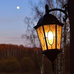 Lighted street lamp against the beautiful spring landscape with the moon in sky and birch during sunset. Russia, Moscow region
