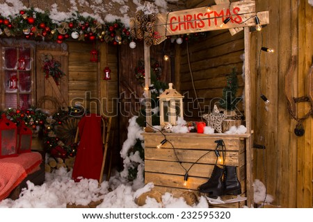 Lighted Wooden Christmas Booth Inside a House with Various Christmas Decorations.