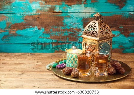 Lightened lantern, tea cups and dates on wooden table over rustic background. Ramadan kareem holiday celebration concept