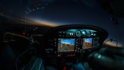 Lightened up cockpit and avionics in aircraft flying at night with beautiful twilight in background