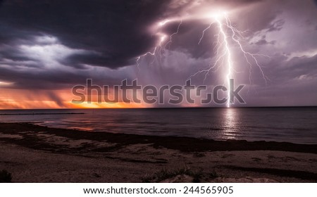 Lightening storm moving in over beach at sunset.
