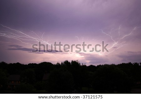 Lightening strike over woods and houses