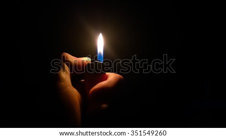 Lighter in a Hand Against Black Backdrop Photo stock ©