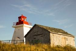 Lighthouse against blue skies in Cape Breton Highlands National Park, Nova Scotia, Canada.