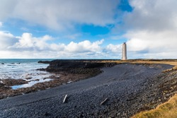 Lighthouse along the West Coast of Iceland on a Sunny Autumn Day. A Small Black Pebble Beach is in Foreground. A Lonely Person admiring the Scenery is at the Bottom of the Lighthouse.