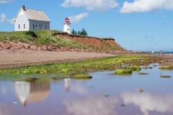 Lighthouse and building perched on red sandstone cliffs on a sunny day at Panmure Island, PEI, with reflections in the water at low tide