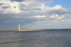 Lighthouse and cumulus clouds. Reflection of clouds by water. Contrasting clouds in light and subtle colors