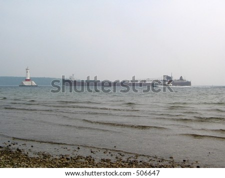 lighthouse and large freighter on lake huron as seen from the beach of Mackinac Island #506647