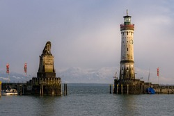 lighthouse and lion at largest german lake with mountains in the background at day