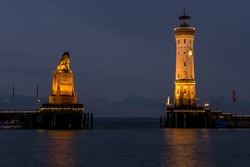lighthouse and lion at largest german lake with mountains in the background at night