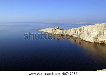 Lighthouse and the ruins of the far south point of the island Pag in Croatia - stock photo