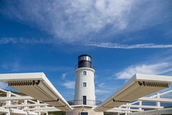 Lighthouse and watch tower - light beacon warning signal for the safety of nautical navigation at sea or ocean against clouds in blue sky on a sunny day, behind white wings like structure.