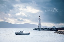 Lighthouse and white fishing boat over the calm sea on a cloudy winter morning in Turgutreis harbor, Bodrum, Turkey.