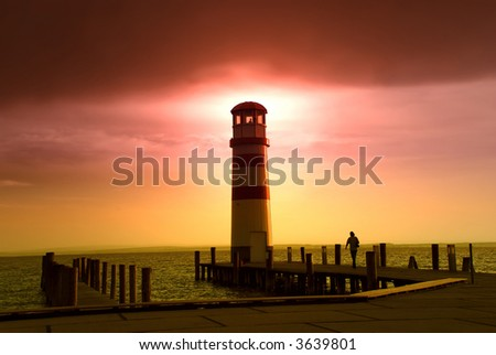 Lighthouse at an Austrian lake with a woman walking towards it