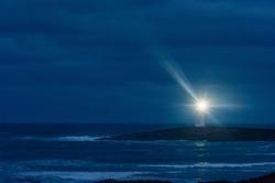 Lighthouse at night under heavy cloud on dark peninsula