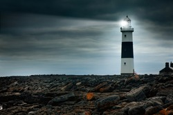 lighthouse at night with spotlight beam. Ireland