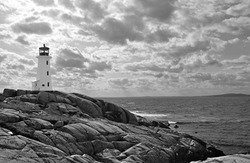 Lighthouse at Peggy's Cove, Nova Scotia.  In black and white with dramatic clouds in sky.