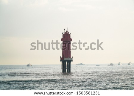 Lighthouse at seashore Sanur beach  Bali . Fast boat behind the red  lighthouse on the sea of Sanur in the morning