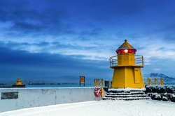 Lighthouse at the entrance to the Old Port, Reykjavik, Iceland. Blue hour shot at dawn during winter, with yellow beacons and snow on the ground.