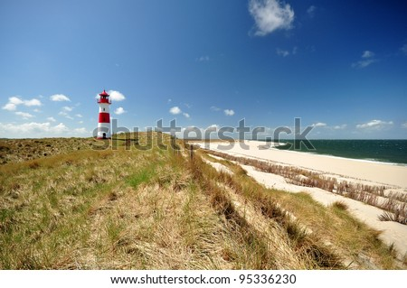 Lighthouse at the German North Sea island Sylt in the dunes at the beach with blue sky. - stock photo