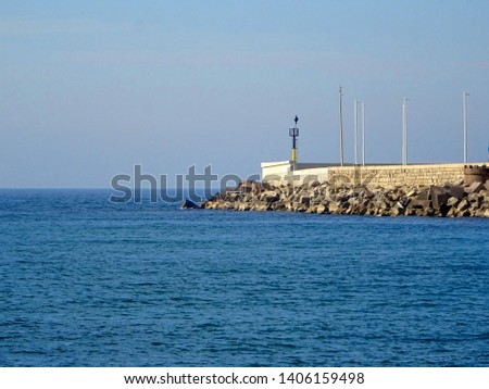 lighthouse at the tip of the harbor breakwater with sea in the background #1406159498