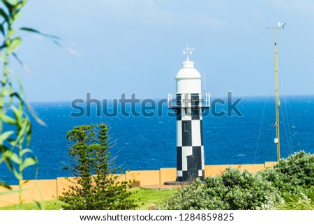 Lighthouse beacon black and white structure building on headland point  overlooking windy blue ocean for shipping marine night safety. #1284859825
