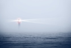 Lighthouse in a foggy sea show the direction - loneliness and hope concept