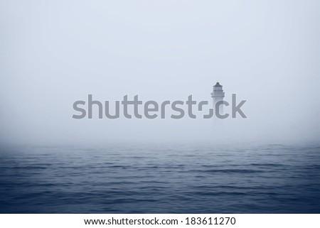 Lighthouse in misty sea