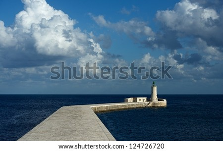 Lighthouse in the blue sea with clouds formation, nice sea view with lighthouse and small birds in Malta, way to the lighthouse from the new Grand Harbour Bridge in Valletta, Valletta lighthouse,Malta
