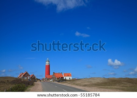 Lighthouse in the dunes at the beach with blue sky - stock photo