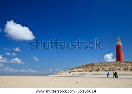 Lighthouse in the dunes at the beach with blue sky