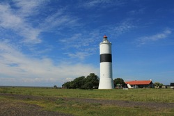Lighthouse, Lange Jan (Långe Jan) on the coast side with a blue sky and open field in front, Öland, Sweden