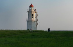 Lighthouse on a background of blue sky. Silhouettes of people.