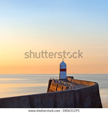 Lighthouse on breakwater wall with calm sea during sunrise.  Tranquil scene on Isle of Man