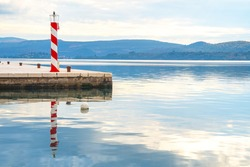 Lighthouse on coast to serve as navigational aid at sea, mark dangerous coastlines, hazardous shoals, reefs, rocks and safe entries to harbors. Calm mirror surface of water