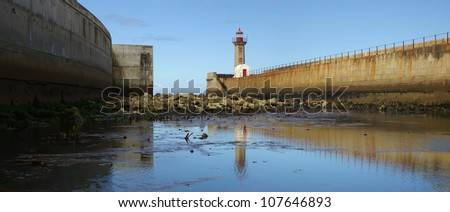 Lighthouse on Foz do Douro - Portugal at low tide and early morning light.(panoramic picture,not a crop)